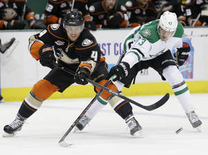 Photo - Anaheim Ducks defenseman Cam Fowler (4) passes the puck as Dallas Stars right wing Valeri Nichushkin (43) tries to block during the first period of an NHL hockey game in Dallas, Tuesday, Nov. 26, 2013.  (AP Photo/Tim Sharp)
