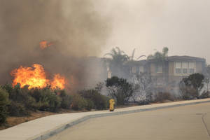 Photo - A wildfire climbs a canyon toward homes Wednesday, May 14, 2014, in Carlsbad, Calif. More wildfires broke out Wednesday in San Diego County — threatening homes in Carlsbad and forcing the evacuations of military housing and an elementary school at Camp Pendleton — as Southern California is in the grip of a heat wave. (AP Photo)