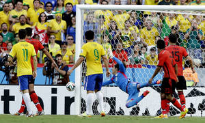 Photo - Mexico's goalkeeper Guillermo Ochoa, center, makes a save during the group A World Cup soccer match between Brazil and Mexico at the Arena Castelao in Fortaleza, Brazil, Tuesday, June 17, 2014. (AP Photo/Andre Penner)