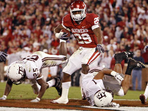photo - Oklahoma's Chris Brown (29) makes his way into the endzone past Texas A&M's Jordan Pugh (25) and Trent Hunter (1) during the second half of the college football game between the University of Oklahoma Sooners (OU) and the Texas A&M Aggies at Gaylord Family-Memorial Stadium on Saturday, Nov. 14, 2009, in Norman, Okla. Photo by Chris Landsberger, The Oklahoman