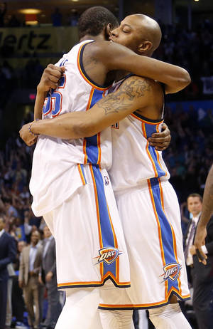 Photo - Oklahoma City's Kevin Durant (35) hugs Caron Butler (2) after the 112-111 win over Detroit during the NBA basketball game between the Oklahoma City Thuder and the Detroit Pistons at Chesapeake Energy Arena in Oklahoma City, Okla. on Wednesday, April 16, 2014.  Photo by Chris Landsberger, The Oklahoman