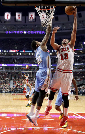 Photo - Chicago Bulls center Joakim Noah (13) shoots over Denver Nuggets forward Wilson Chandler (21) during the first half of an NBA basketball game Friday, Feb. 21, 2014, in Chicago. (AP Photo/Charles Rex Arbogast)
