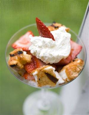 Photo - This May 30, 2012 image shows a dessert of spiced and grilled angel food cake with strawberries and whipped cream in Concord, N.H. (AP Photo/Matthew Mead)