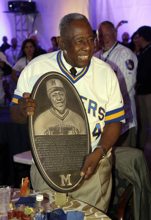 Photo - Hank Aaron holds a replica of a plaque that will be displayed on the new Milwaukee Brewers Wall of Honor before a baseball game between the Brewers and the Cincinnati Reds, Friday, June 13, 2014, in Milwaukee. (AP Photo/Morry Gash)