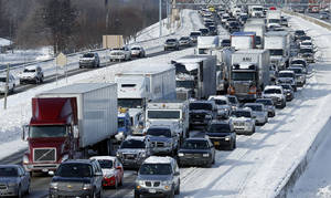 Photo - Traffic backs up along I-75 due to icy conditions on pavement in Detroit, Tuesday, Jan. 7, 2014. Temperatures broke record lows Tuesday in Michigan and residents braced against bitter winds following a multiday storm that shuttered schools, closed government offices and contributed to at least six deaths.   (AP Photo/Paul Sancya)