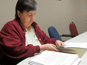 photo - Right: Glenda Hey, 60, sorts a pile of documents and correspondence recently from American Trade Association's health care plan.   PHOTO BY VALLERY BROWN,  THE OKLAHOMAN