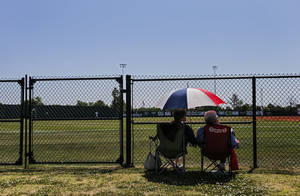 Photo - Fans take in the game from under an umbrella during the Class 5A baseball state tournament game between Guthrie and Shawnee at Norman North High School in Norman, Okla. on Thursday, May 15, 2014.   Photo by Chris Landsberger, The Oklahoman