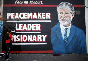 Photo - A man adds the finishing touch to a newly painted mural of Gerry Adams on the Falls Road, West Belfast, Northern Ireland, Northern Ireland, Friday, May, 2 2014.  Police continue to question the Sinn Fein leader Gerry Adams at Antrim police station about the 1972 murder of Jean McConville.  (AP Photo/Peter Morrison)