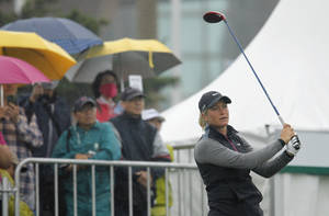 Photo - Despite the rain and poor visibility, Suzann Pettersen of Norway, tees off on the first day of the Sunrise LPGA Taiwan Championship tournament at the Sunrise Golf & Country Club, Thursday, Oct. 24, 2013, in Yangmei, north eastern Taiwan. (AP Photo/Wally Santana)