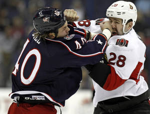 Photo - Columbus Blue Jackets' Jared Boll, left, fights Ottawa Senators' Matt Kassian in the first period of an NHL hockey game in Columbus, Ohio, Tuesday, Nov. 5, 2013. (AP Photo/Paul Vernon)