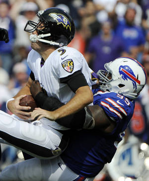 Photo - Baltimore Ravens quarterback Joe Flacco (5) is sacked by Buffalo Bills defensive tackle Marcell Dareus (99) during the first half of an NFL football game on Sunday, Sept. 29, 2013, in Orchard Park, N.Y. (AP Photo/Gary Wiepert)