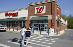 Photo - In this Wednesday, May 14, 2014 photo, customers walk toward an entrance to a Walgreens store location, in Boston. Walgreen Co. reports quarterly earnings on Tuesday, June 24, 2014. (AP Photo/Steven Senne)