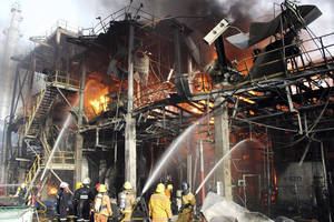 Photo -   In this photo taken Saturday, May 5, 2012, Thai firefighters try to put off the fire after an explosion at a factory in Rayong province, Thailand. A fire caused by explosions in one of the world's largest petrochemical industrial estates have killed 12 and injured more than 100 people in eastern Thailand. (AP Photo)