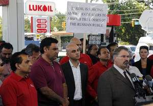 Photo -   Sal Risalvato, second right, answers a question at a Lukoil service station Wednesday, Sept. 12, 2012, in South Plainfield, N.J., as a large gathering of Lukoil dealers and workers protested what they say are unfair pricing practices by Lukoil North America. More than 50 Lukoil gas stations in New Jersey and Pennsylvania were jacking up prices to more than $8 a gallon Wednesday to protest what they say are unfair pricing practices by Lukoil North America that they say leave them at a competitive disadvantage. Risalvato of the New Jersey Gasoline, Convenience, Automotive Association said the protest was aimed at raising consumer awareness about the challenges facing Lukoil dealers and to get Lukoil to respond to dealer grievances. (AP Photo/Mel Evans)