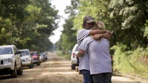 Photo - Peter Placker and his daughter Linda comfort each other following a press conference held at the site where Taylor Paschal-Placker, 13, and her friend Skyla Jade Whitaker, 11, were killed on a country road just north of Weleetka. Tuesday marked the two-year anniversary of the killings. ADAM WISNESKI/Tulsa World