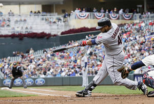 Photo - Cleveland Indians' Carlos Santana hits a rwo-run home run off Minnesota Twins pitcher Cole DeVries in the fourth inning of a baseball game on Saturday, Sept. 28, 2013, in Minneapolis. (AP Photo/Jim Mone)
