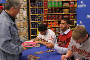 Photo - Paul Marquez of Miami, Oklahoma gets autographs from Jose Altuve and other Astros players J.D. Martinez and David Carpenter at Academy Sports Store Monday, February 6, 2012. PHOTO BY HUGH SCOTT, FOR THE OKLAHOMAN ORG XMIT: KOD