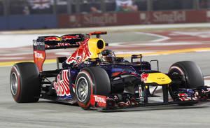 Photo -   Red Bull Formula One driver Sebastian Vettel of Germany steers his car during the Singapore Formula One Grand Prix on the Marina Bay City Circuit in Singapore, Sunday, Sept. 23, 2012. (AP Photo/Dita Alangkara)