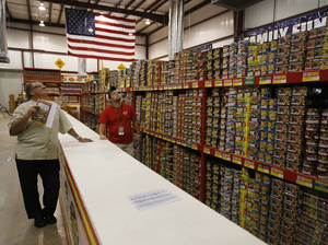 photo - Cody Compton (right) helps Phil LaRue, of Edmond, look for fireworks at TNT Fireworks Supercenter in Mustang, Tuesday, June 26, 2012.  Photo by Garett Fisbeck, The Oklahoman