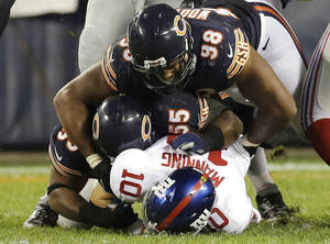 Photo - New York Giants quarterback Eli Manning (10) gets sacked by Chicago Bears linebacker Lance Briggs (55) and defensive end Corey Wootton (98) in the second half of an NFL football game, Thursday, Oct. 10, 2013, in Chicago. (AP Photo/Nam Y. Huh)