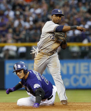Photo - Milwaukee Brewers shortstop Jean Segura, back, throws to first base after forcing out Colorado Rockies' Troy Tulowitzki at second base in the fourth inning of a baseball game in Denver on Saturday, July 27, 2013. (AP Photo/David Zalubowski)