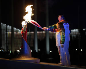Photo - Irina Rodnina and Vladislav Tretiak light the Olympic cauldron during the opening ceremony of the 2014 Winter Olympics in Sochi, Russia, Friday, Feb. 7, 2014. (AP Photo/Matt Slocum, Pool)