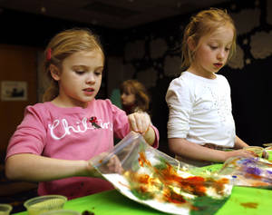 photo - Greta Mansell, 7, and Lydia Stuart, 8, make paintings inside plastic bags during the after-school special story time at the Norman Public Library. PHOTO BY STEVE SISNEY, THE OKLAHOMAN <strong>STEVE SISNEY</strong>