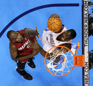 photo - Oklahoma City's Serge Ibaka (9) dunks the ball past Miami's Joel Anthony (50) during the NBA basketball game between the Miami Heat and the Oklahoma City Thunder at Chesapeake Energy Arena in Oklahoma City, Sunday, March 25, 2012. Oklahoma City won, 103-87. Photo by Nate Billings, The Oklahoman