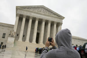 Photo - FILE - This April 29, 2014 file photo shows a Supreme Court visitor using his cellphone to take a photo of the court in Washington. A unanimous Supreme Court says police may not generally search the cellphones of people they arrest without first getting search warrants. The justices say cellphones are powerful devices unlike anything else police may find on someone they arrest.  (AP Photo, File)