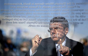 Photo - International Olympic Committee President Thomas Bach signs the Olympic truce wall during a ceremony in the Coastal Cluster Olympic Village at the 2014 Winter Olympics, Tuesday, Feb. 4, 2014, in Sochi, Russia. (AP Photo/David Goldman)