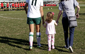 Photo - Bishop McGuinness soccer player Cierra Allen, left, walks with Chloe Hood, 4, of Good Shepherd Catholic School at Mercy. Photo by Sarah Phipps, The Oklahoman
