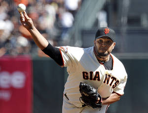 Photo - San Francisco Giants pitcher Yusmeiro Petit (52) throws against the San Diego Padres during the first inning of a baseball game on Saturday, Sept. 28, 2103,  in San Francisco. (AP Photo/Tony Avelar)