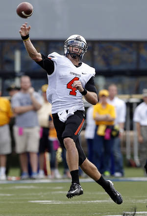 Photo - Oklahoma State's J.W. Walsh (4) throws a pass during a college football game between the Oklahoma State University and West Virginia University on Mountaineer Field at Milan Puskar Stadium in Morgantown, W. Va.,   Saturday, Sept. 28, 2013. Photo by Sarah Phipps, The Oklahoman