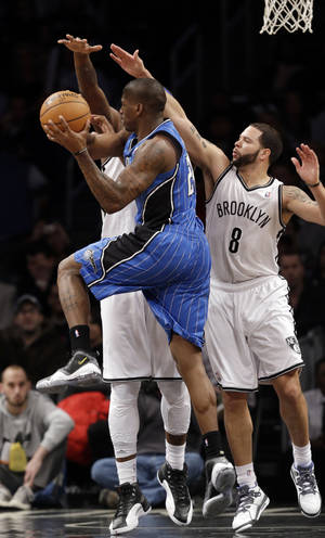 photo - Orlando Magic forward DeQuan Jones (20)  passes as he is double-teamed by Brooklyn Nets guard Deron Williams (8) and Brooklyn Nets forward Andray Blatche (0) in the first half of their NBA basketball game at the Barclays Center, Monday, Jan. 28, 2013 in New York. (AP Photo/Kathy Willens)