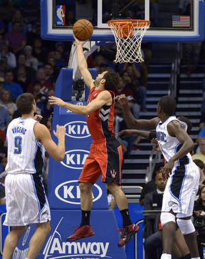 photo - Toronto Raptors guard Jose Calderon, center, of Spain, puts up a shot between Orlando Magic center Nikola Vucevic (9), of Montenegro, and forward Andrew Nicholson, right, during the first half of an NBA basketball game in Orlando, Fla., Saturday, Dec. 29, 2012. (AP Photo/Phelan M. Ebenhack)