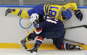 Photo - Julie Chu of the United States collides with Anna Borgqvist of Sweden during the first period of the 2014 Winter Olympics women's semifinal ice hockey game at Shayba Arena Monday, Feb. 17, 2014, in Sochi, Russia. (AP Photo/Matt Slocum)