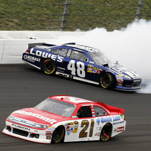 Photo -   Trevor Bayne (21) passes Jimmie Johnson (48) as Johnson hits the wall during a NASCAR Sprint Cup Series auto race at Kansas Speedway in Kansas City, Kan., Sunday, Oct. 21, 2012. (AP Photo/Colin E. Braley)