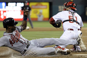 Photo - Atlanta Braves' B.J. Upton, left, beats a tag by Philadelphia Phillies' Carlos Rui, right,  and scores on a Tim Hudson single in the fifth inning of a baseball game on Saturday, July 6, 2013, in Philadelphia. (AP Photo/Michael Perez)