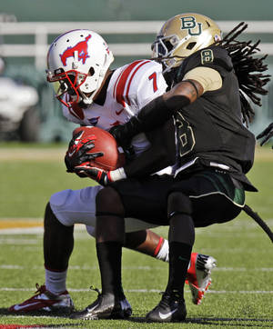 Photo -   Southern Methodist wide receiver Der'rikk Thompson (7) is wrapped up by Baylor safety K.J. Morton (8) after catching a pass during the first half of an NCAA college football game in Waco, Texas, Sunday, Sept. 2, 2012. (AP Photo/LM Otero)