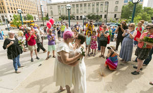 Photo - Cody Huston, left, and Tina Cady, both of Madison, embrace after getting married Saturday, June 7, 2014, in Madison, Wis. On Friday a federal judge struck down the state's gay marriage ban. (AP Photo/Andy Manis)