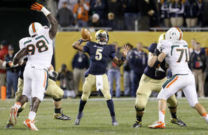 Photo -   Notre Dame quarterback Everett Golson (5) passes between the Miami defense of defensive lineman Darius Smith, left, and defensive lineman Anthony Chickillo (71) during the first half of an NCAA college football game at Soldier Field Saturday, Oct. 6, 2012, in Chicago. (AP Photo/Charles Rex Arbogast)