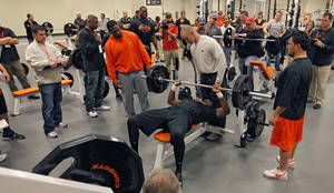 Photo - NFL scouts look on as Oklahoma State football players bench press 225 pounds during the NFL pro day at Oklahoma State University on Wednesday, March 9, 2011, in Stillwater, Okla.  Photo by Chris Landsberger, The Oklahoman