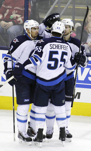 Photo - Winnipeg Jets' Evander Kane, left, celebrates his game-winning goal against the Columbus Blue Jackets with teammates Mark Scheifele, center, and Michael Frolik, of Check Republic, during the third period of an NHL hockey game Monday, Dec. 16, 2013, in Columbus, Ohio. The Jets won 3-2. (AP Photo/Jay LaPrete)