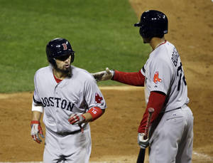 Photo - Boston Red Sox's Shane Victorino, left, is congratulated by Xander Bogaerts after scoring during the sixth inning of Game 3 of baseball's World Series against the St. Louis Cardinals Saturday, Oct. 26, 2013, in St. Louis. (AP Photo/Charlie Neibergall)