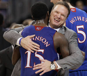 Photo - Kansas coach Bill Self celebrates with guard Elijah Johnson during the second half of the NCAA men's college basketball tournament Midwest Regional final against North Carolina on Sunday, March 25, 2012, in St. Louis. Kansas won 80-67. (AP Photo/Charlie Riedel)