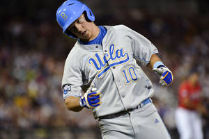 Photo -   UCLA's Pat Valaika reacts to being thrown out by Arizona shortstop Alex Mejia in the seventh inning of an NCAA College World Series baseball game in Omaha, Neb., Sunday, June 17, 2012. (AP Photo/Ted Kirk)