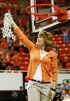 photo - Shelley Budke, widow of OSU head coach Kurt Budke, points upwards after cutting down the last of the net after the OSU Cowgirls won the Women's NIT championship college basketball game between Oklahoma State University and James Madison at Gallagher-Iba Arena in Stillwater, Okla., Saturday, March 31, 2012. Kurt Budke and three others were killed in a plane crash on a recruiting trip in November of 2011. OSU won, 75-68. Photo by Nate Billings, The Oklahoman