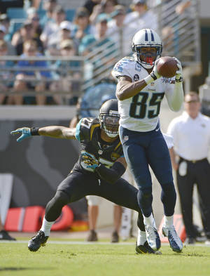 Photo - Tennessee Titans wide receiver Nate Washington (85) catches a pass in front of Jacksonville Jaguars cornerback Dwayne Gratz (27) during the first half of an NFL football game in Jacksonville, Fla., Sunday, Dec. 22, 2013. (AP Photo/Phelan M. Ebenhack)