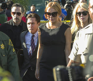 Photo - Lindsay Lohan, third from left, her mother Dina Lohan, right, her new attorney Mark Heller, second from left, leave a Los Angeles court, Wednesday, Jan. 30, 2013, in a case filed over the actress' car crash last June. A judge has delayed Lindsay Lohan's trial on three misdemeanor counts. She pleaded not guilty to lying to police, reckless driving and obstructing officers from performing their duties. (AP Photo/Damian Dovarganes)