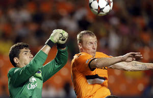 Photo - Everton goalkeeper Joel Robles, left, punches the ball as Valencia defender Jeremy Mathieu challenges during the first half of an International Champions Cup soccer match, Tuesday, Aug. 6, 2013, in Miami. (AP Photo/Wilfredo Lee)